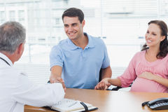 Smiling man shaking hands with his doctor while holding his expe Royalty Free Stock Images