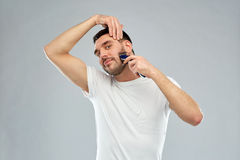 Smiling man shaving beard with trimmer over gray Stock Images