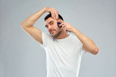 Smiling man shaving beard with trimmer over gray Royalty Free Stock Photos