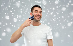 Smiling man shaving beard with trimmer over snow Stock Photo