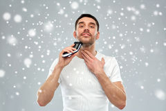 Smiling man shaving beard with trimmer over snow Stock Photos