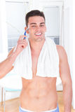 Smiling man shaving face with razor. Morning shaving, half naked guy with towel around neck shaving royalty free stock photos