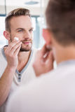 Smiling man shaving his beard. In bathroom Royalty Free Stock Photography
