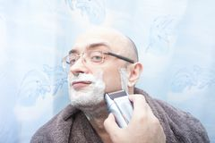 Smiling man shaving his beard with electric razor. Front view Stock Images
