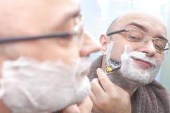 Smiling man shaving his beard at mirror in bathroom. Smiling man shaving his beard at mirror close up Stock Image