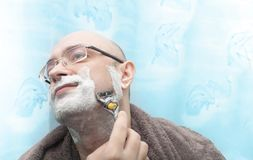 Smiling man shaving his beard by razor blade. And look side Royalty Free Stock Photos
