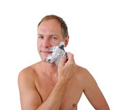 Smiling man shaving with razor and foam Stock Photo