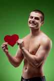 Smiling man shirtless holding heart shape,. Smiling male model shirtless holding heart shape, over green background Royalty Free Stock Images