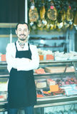 Smiling man shop assistant demonstrating sorts of meat in shop Stock Images