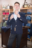 Smiling man shopper searching new suit. In male clothing shop Royalty Free Stock Photos