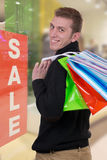 Smiling man with shopping bags in a clothing store Royalty Free Stock Photography