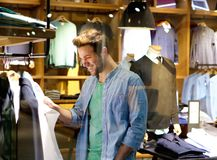 Smiling man shopping for clothes at clothing store royalty free stock photos