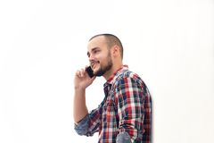 Smiling man with short hair and beard using mobile phone Royalty Free Stock Image