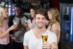 Smiling man showing a beer with his friends Royalty Free Stock Image