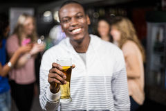 Smiling man showing a beer with his friends Royalty Free Stock Photography