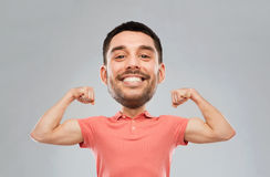 Smiling man showing biceps over gray background Royalty Free Stock Photos