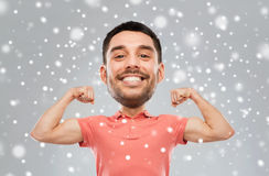 Smiling man showing biceps over snow background Stock Photography