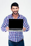 Smiling man showing blank laptop computer screen. Portrait of a smiling man showing blank laptop computer screen isolated on a white background Royalty Free Stock Images