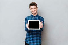 Smiling man showing blank screen of tablet computer. Young smiling man showing blank screen of tablet computer horizontally stock photo