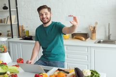 Smiling man showing credit card at table with laptop in kitchen. At home stock image