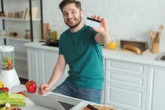 Smiling man showing credit card at table with laptop in kitchen. At home stock photo