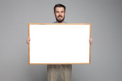 The smiling man showing empty white billboard or Royalty Free Stock Photos