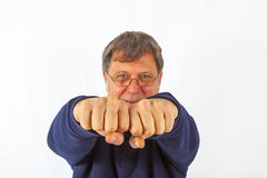 Smiling man is showing his fist. On the white background Stock Photography