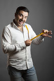 The smiling man showing his sex length. The young man smiles and shows off his sex length with a tape measure Royalty Free Stock Photo