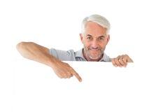 Smiling man showing large poster Royalty Free Stock Image