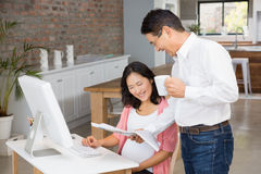 Smiling man showing newspaper to his pregnant wife Stock Photography