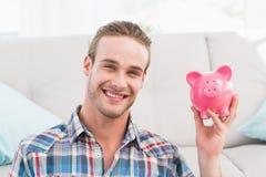 Smiling man showing pink piggy bank Royalty Free Stock Photos