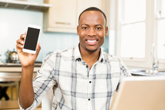 Smiling man showing smartphone screen Royalty Free Stock Image