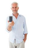 Smiling man showing smartphone to camera Stock Images