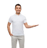 Smiling man showing something on empty palm Stock Photo