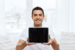 Smiling man showing tablet pc blank screen at home Stock Images