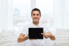 Smiling man showing tablet pc blank screen at home Royalty Free Stock Photos
