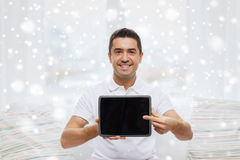 Smiling man showing tablet pc blank screen at home Stock Photo