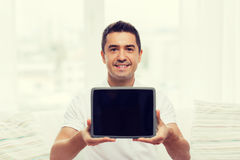 Smiling man showing tablet pc blank screen at home Royalty Free Stock Photography