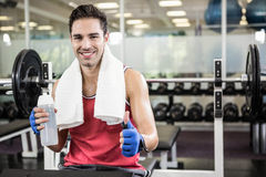 Smiling man showing thumb up and holding bottle of water Stock Photo