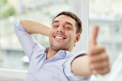 Smiling man showing thumbs up at home or office Royalty Free Stock Images