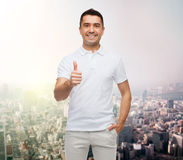 Smiling man showing thumbs up over city background Royalty Free Stock Photo