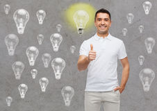 Smiling man showing thumbs up over lighting bulbs. Happiness, gesture and people concept - smiling man showing thumbs up over gray background with lighting bulbs royalty free stock image