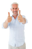 Smiling man showing thumbs up to camera Stock Photo