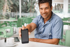 Smiling man showing you blank smartphone Royalty Free Stock Photography