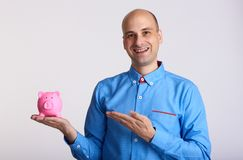Smiling man shows a piggy bank Royalty Free Stock Image