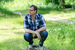 Smiling man sits on lawn of forest. On stone in sunny summer day Royalty Free Stock Photos