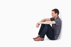 Smiling man sitting against a wall Stock Image