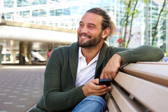 Smiling man sitting on bench outdoors holding smart phone Royalty Free Stock Photo