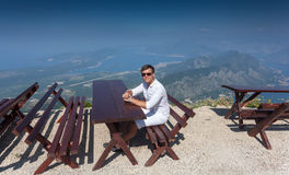Smiling man sitting on bench at top of high mountain at sunny da Stock Images