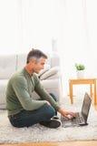 Smiling man sitting on carpet using laptop Royalty Free Stock Images